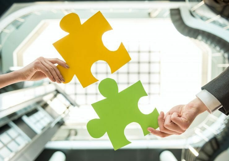 Close-up of business people wanting to put two pieces of puzzle together.